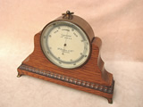 Late Victorian brass cased aneroid barometer  by Francis Darton with oak mantle stand.
