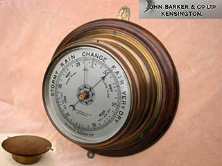 Ships bulkhead barometer with silvered aluminium dial and carries the name John Barker & Co Ltd, Kensington