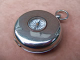 Pocket compass with collapsible stirrup cup inside