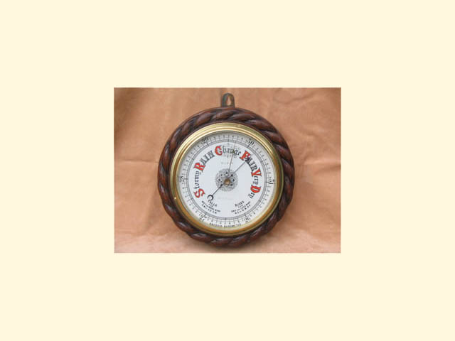 Mahogany cased rope twist aneroid barometer by G R Eve & Co